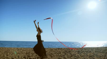 gymnasta : A young woman in a black dress is running on the sand and doing a drawing of a red ginastic ribbon