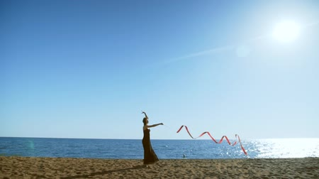 fitas : A young woman in a black dress is standing on the sand and doing a drawing of a red ginastic ribbon Vídeos