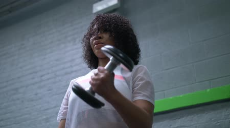 súlyzó : African American woman working with dumbbells in the gym Stock mozgókép