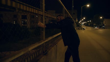 фокус : The man stand on the street. Evening night time. Man looking on downtown through the fence.