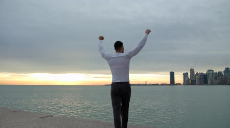 atleta : Fit muscular man goes and stops on the beach with his arms in the air. City, sea and sunrise on the background. He is a winner.