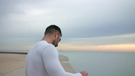 kulturystyka : Fit muscular man is putting the headphone in the ear and starts running. Sea on the background.