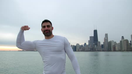 jimnastik : Male athlete is showing his biceps and muscular body and smiling. Sea on the background. Stok Video