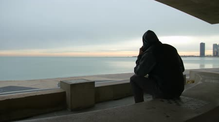 созерцать : Man is sitting on the bench talking on the phone and looking at the sea Стоковые видеозаписи