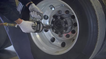 zmiany : Mechanic is changing truck tire in the autorepair service center. Mechanic is unscrewing nuts. Wideo