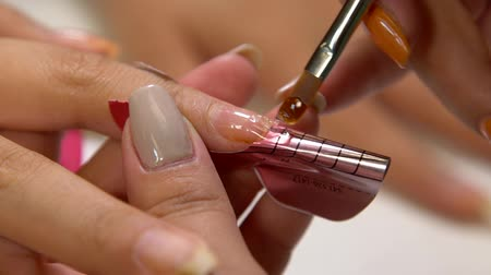 manicure : Close up of a manicurist filing womans nails in the salon.