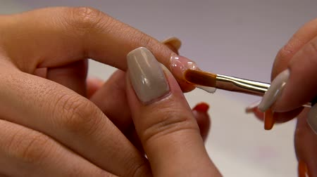 faíscas : Close up of a manicurist filing womans nails in the salon.