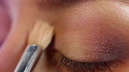 contornos : Close up of makeup artist is applying eyeshadow powder on the womans eyelid