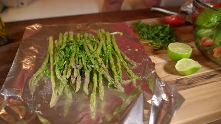 salata : The woman is cooking fresh and tasty asparagus in the foil. Close view. Sprinkle with lime juice.