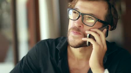 общаться : Close up on the young handsome man is speaking on the smartphone.