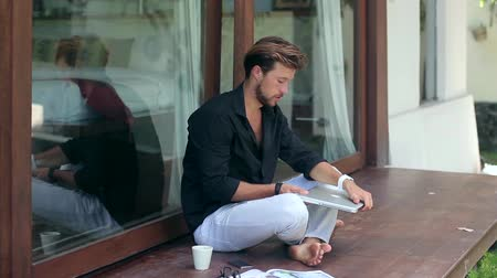czytanie : Young handsome man is sitting down on the terrace and using a laptop outside the house.