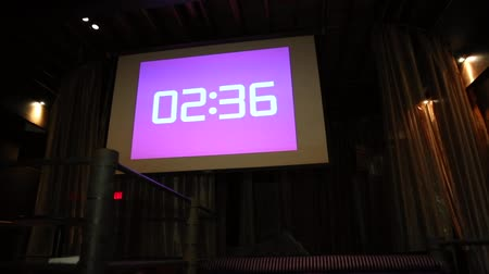 sınırları : projector in action with illuminated warm pink screen and timer