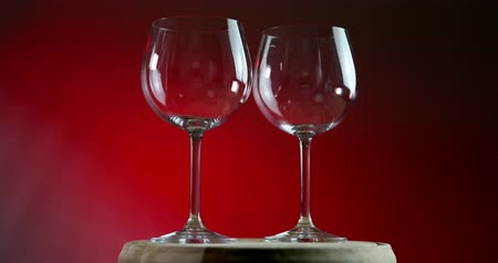 zastawa stołowa : Two empty glasses for wine on a red background rotates on wooden platform