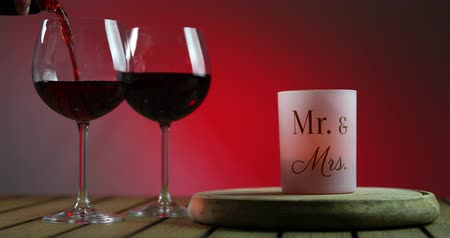 pincészet : Two glasses of red wine standing on a table with candle on the wooden platform. Waiter pouring wine into the wineglass. Stock mozgókép