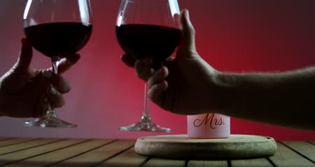 pincészet : Couple clinks glasses. Two glasses of red win with candle on the wooden platform. Cheers.