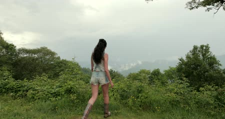 Woman is walking close to the mountain edge.