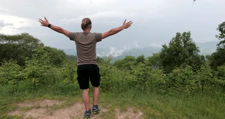 épico : Man is walking close to the mountain edge and raising his hands to the sky. Stock Footage
