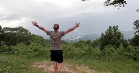 Man is walking close to the mountain edge and raising his hands to the sky. Wideo