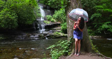 Young woman standing in the forest with an umbrella near waterfall and looks at the falling water. Wideo