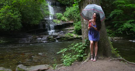 Young woman standing in the forest with an umbrella near waterfall and looks at the falling water. Stok Video