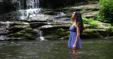 Young woman standing in the river near waterfall and looking at the falling water. Woman is smiling and breathing deeply.