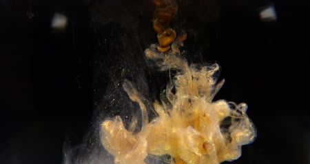 Golden paint cloud with glitter in water isolated on black background