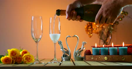 Bottle of champagne opening.С ork flies out. Two glasses. Man pours champagne into glasses. Romantic evening. Stok Video