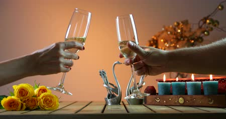 Couple tinkles glasses. Two glasses of champagne, candles on the wooden table. Cheers. Romantic evening.