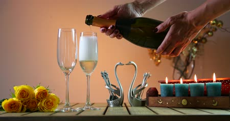 Bottle of champagne with two glasses. Woman pours champagne into glasses. Romantic evening.