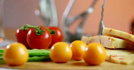 Yellow cheese with fresh vegetables. Tomatoes. Isolated on orange background. Stok Video