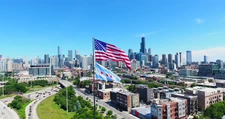 bakış : Aerial drone shot of Chicago downtown above the highway with american flag. USA Flag in the middle.