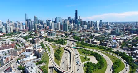 Aerial drone shot of Chicago downtown above the highway with american flag. USA Flag in the middle. Camera tilts up.