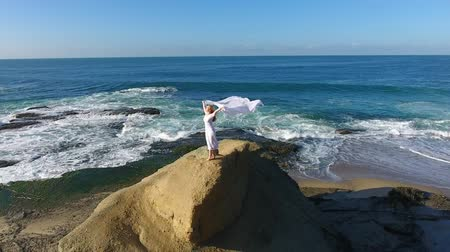 nadzieja : Freedom Concept . Women in white dress and with scarf standing on the Rock. Dancing. Flying. Wideo
