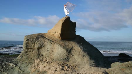 hair dress : Freedom Concept . Women in white dress and with scarf standing on the Rock. Dancing. Flying. Moving.