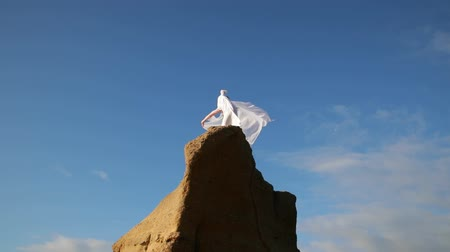 Freedom Concept . Women in white dress and with scarf standing on the Rock. Dancing. Flying. Moving.