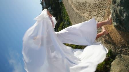 360 shot. Freedom Concept . Women in white dress and with scarf standing on the Rock. Dancing. Flying. Moving.