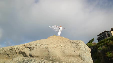 ruha : Freedom Concept . Women in white dress and with scarf standing on the Rock. Dancing. Flying. Moving.