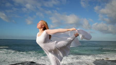 Freedom Concept . Women in white dress and with scarf standing on the Rock. Dancing. Flying. Moving. Doing gymnastic elements.