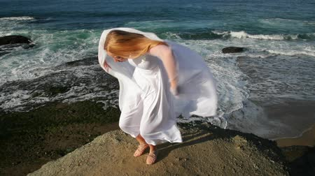 ruha : Freedom Concept . Women in white dress and with scarf standing on the Rock. Dancing. Flying. Moving. Doing gymnastic elements.