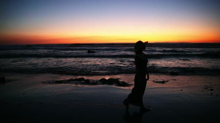 looking far away : woman walking on the beach near the ocean at the sunset Stock Footage