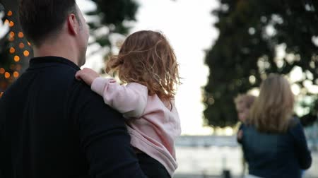 ona : Father kisses his daughter while she is sitting on his hands. They are walking outdoors together. Dostupné videozáznamy