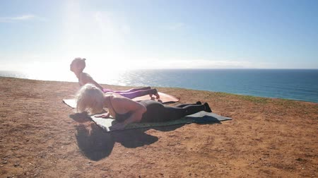 esneme : Fitness, sport, friendship and lifestyle concept - sportive women making yoga exercises sitting on mats in sunny morning outdoors near beautiful ocean on the break.