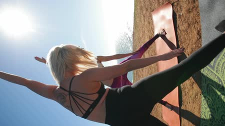 инструктор : Fitness, sport, friendship and lifestyle concept - sportive women making yoga exercises sitting on mats in sunny morning outdoors near beautiful ocean on the break. 360 degrees shot