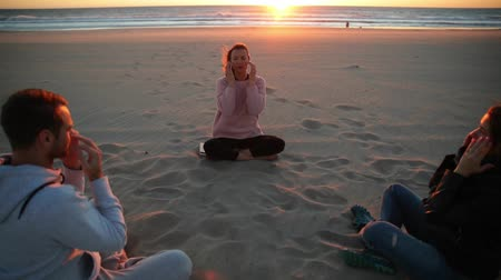 sustentável : Yoga session on the beach with coach men and woman.