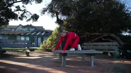 the conception : Young blonde woman in red latex costume is doing yoga exercises on the table in the forest. Stock Footage