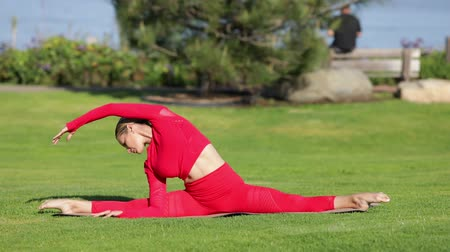 the conception : Young blonde woman in red latex costume is doing yoga exercises.