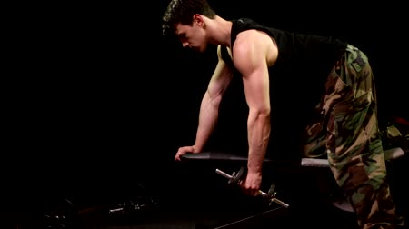 Bent-over row exercise. Studio shot over black.