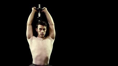 Overhead triceps extension exercise. Studio shot over black.