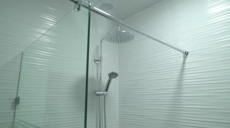 záchod : Room with shower booth made of glass with hand-held adhesive hanging on the wall Dostupné videozáznamy