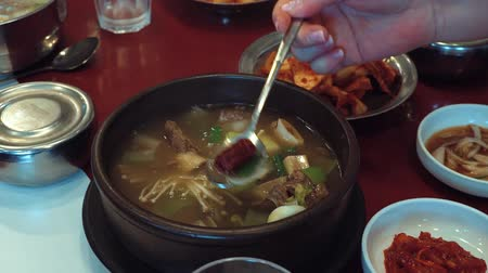 soupe légumes : Hand stirring spoon Korean soup with mushrooms and meat in plate standing on table Vidéos Libres De Droits